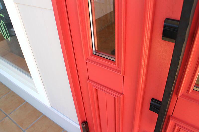 トマト色塗りつぶしの木製玄関ドア