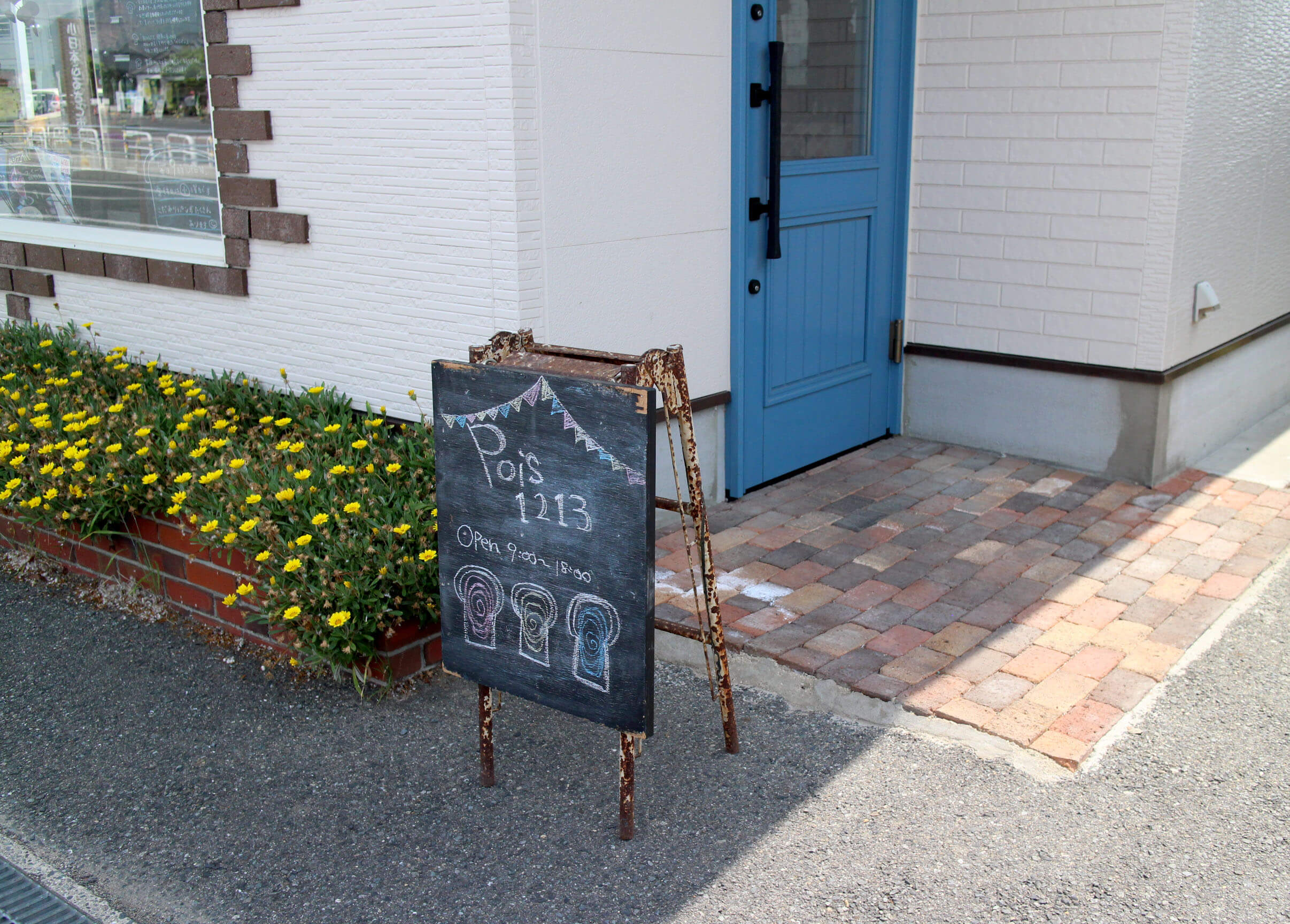 可愛い看板。黄色い花と青い玄関ドア
