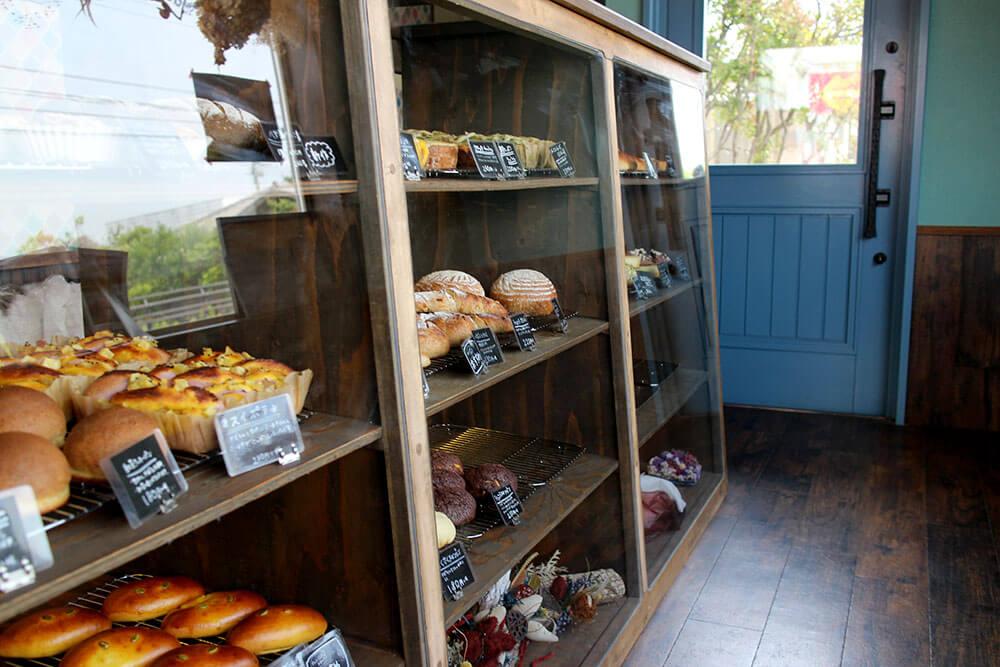 パンが並ぶショーケースとユダ木工の木製ドア
