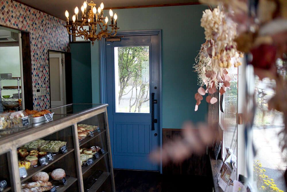 ユダ木工の青い木製玄関ドアと可愛い店内