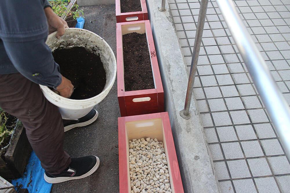 新しくなった木製プランターに土を入れます