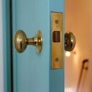 カラフルでかわいい水色の木製室内ドアと、おしゃれな真鍮ノブ