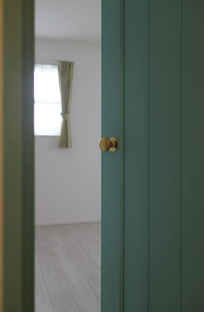 パステルカラーがかわいい、淡いブルーの室内ドアと真鍮ノブ