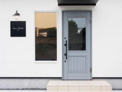 モノトーンの外観がおしゃれな1席限定美容室 me time hair と木製玄関ドア。