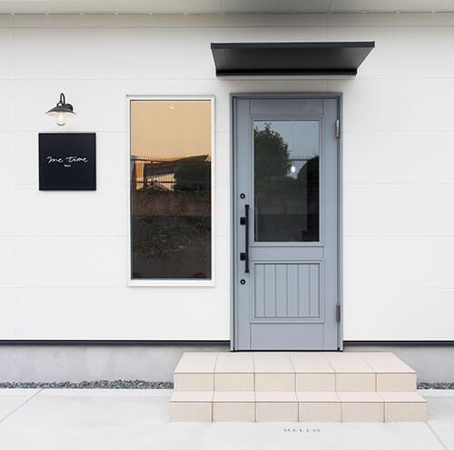 白い壁にグレーの玄関ドア モノトーンがおしゃれな美容室外観