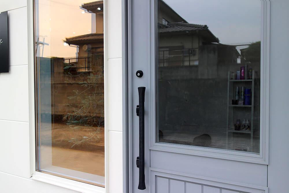 オレンジ色に反射するガラスと、グレーの木製玄関ドア