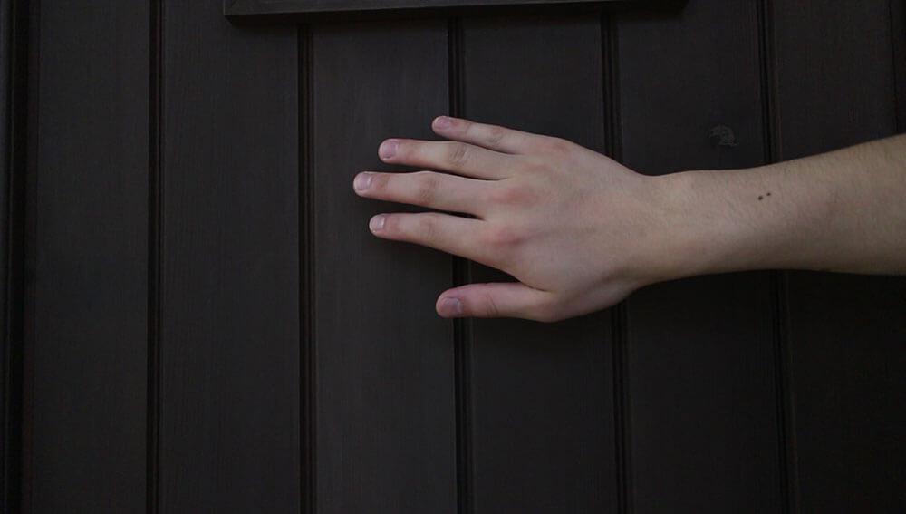 触って感触を確かめる-木製玄関ドアのメンテナンス再塗装