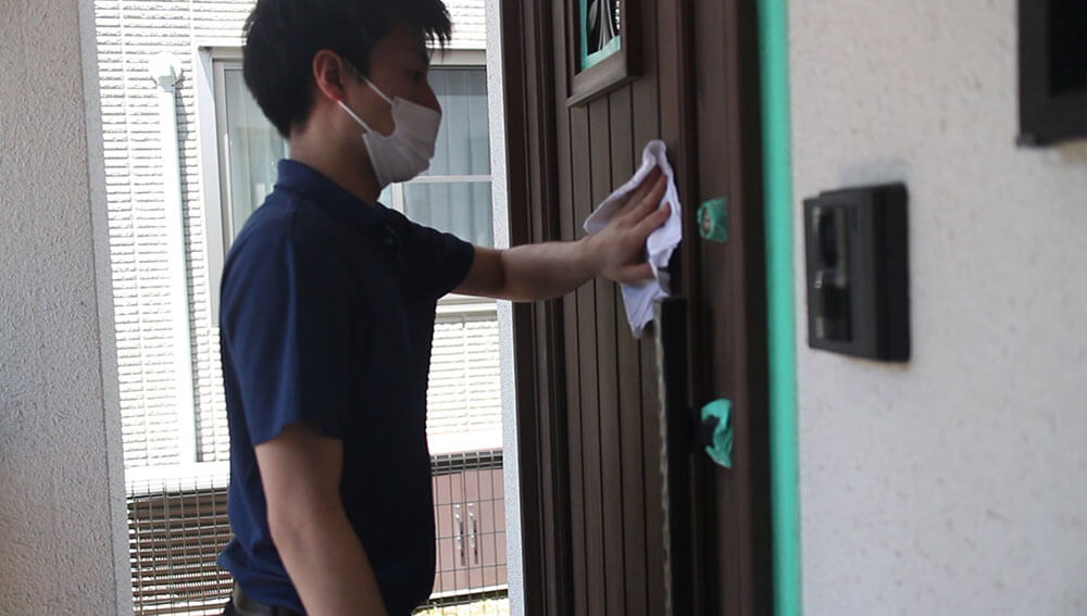 研磨で出た粉を落とす-木製玄関ドアのメンテナンス再塗装