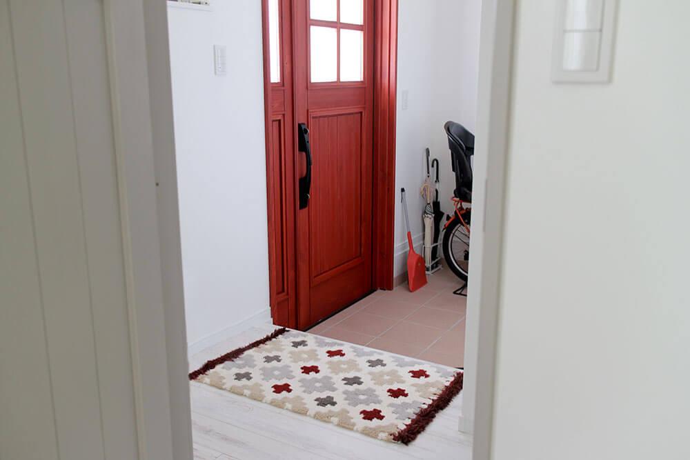 赤い木製玄関ドアとグレーのリビングドア